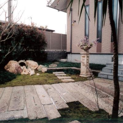 天然の延石を贅沢に使用したアプローチ。シンボルツリーのドラセナがエキゾチックに演出。