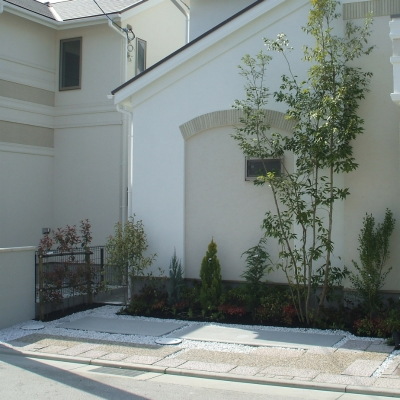 コンクリート、洗い出し、化粧砂利を組み合わせ、建物との境界に植栽を設けたガレージ