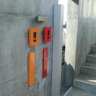 コンクリート打ちっぱなしの塀に映えるポップなカラーのインターホンカバー、ポストが印象的
