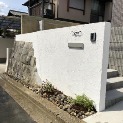既存石積を活用した門柱が特徴的な高低差のある新築外構